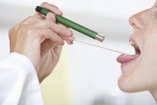 доктор осматривает язык пациента