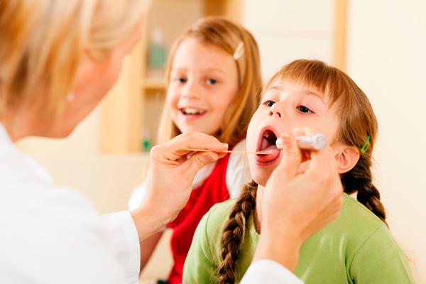 доктор осматривает язык ребенка